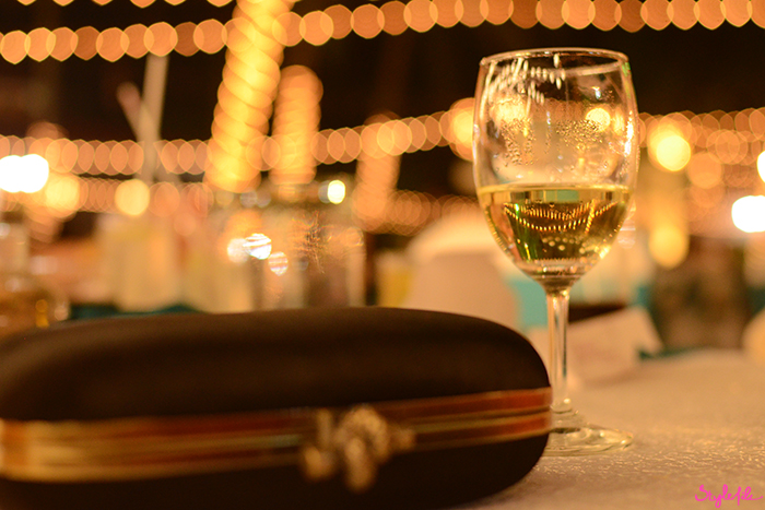 An image of a glass of white wine and a black satin box clutch purse against a bokeh background on a summer holiday break in Goa, India