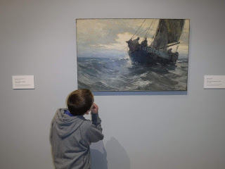 a boy in a great sweatershirt is seen from the back looking at a painting of a ship on a stormy sea at the Sioux City Art Center