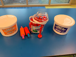 tubs of play dough and letter stampers on top of table