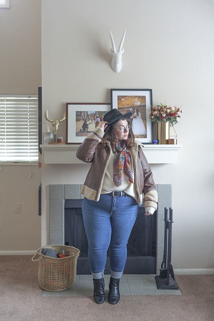 An outfit consisting of a black wide brim hat, a warm toned patterned neck scarf, brown faux leather and faux sherpa moto jacket, a white sweater half tucked into a mid rise jeans and black Chelsea boots.