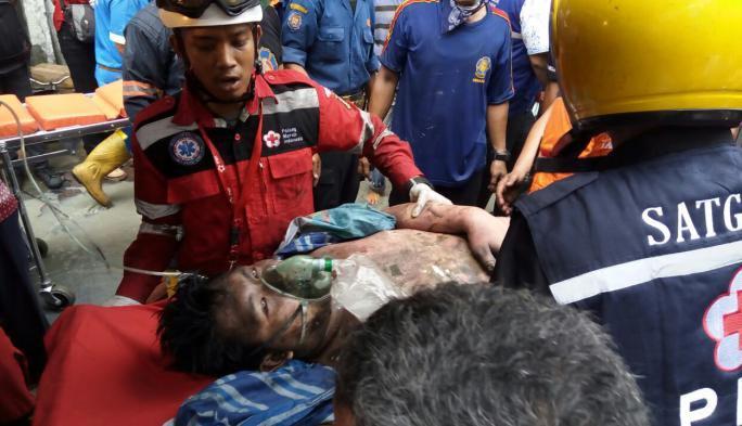 Petugas pemadam kebakaran mengevakuasi korban kebakaran