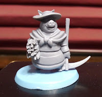 One of the player pieces. A grey plastic miniature of an anthropomorphised pig wearing a sun bonnet and scarf, holding a scythe and a bundle of straw, on a light blue base.