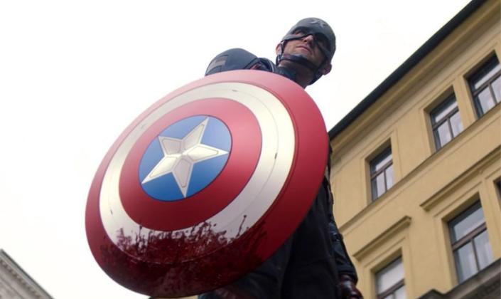 Imagem de capa: o personagem Agente Americano, um homem em traje de Capitão América, um traje azul com um capacete em formato de A e com formato de estrela e um escudo redondo com listras vermelhas, brancas e no centro o círculo azul com uma estrela branca no centro e manchado de sangue.