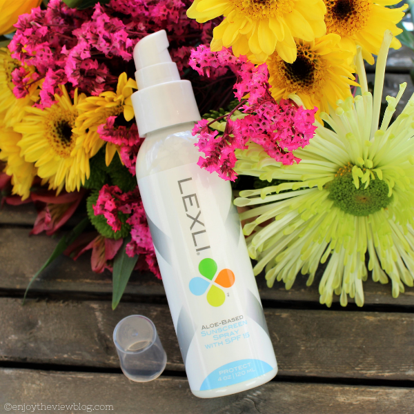bottle of Lexli sunscreen spray lying on yellow and pink flowers