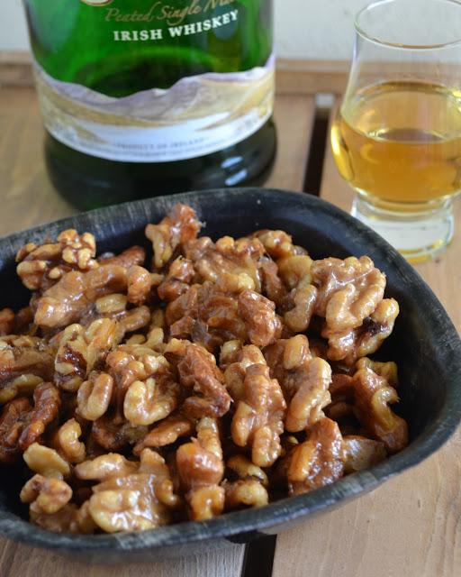 bakje noten met een glaasje whiskey (whisky) ernaast. De fles staat op de achtergrond en de noten hebben een whiskeylaagje.