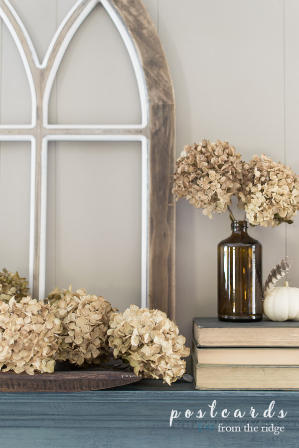 dried hydrangeas and brown bottles on a blue mantel