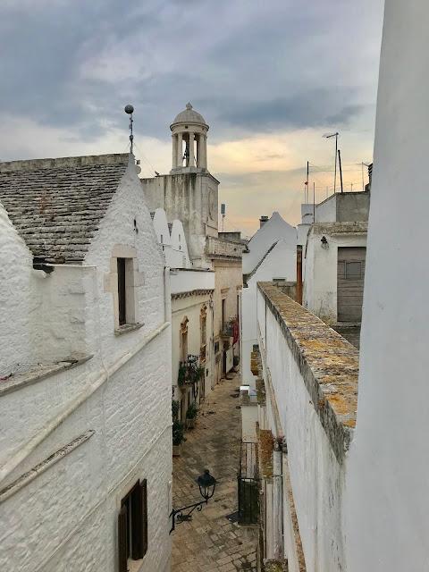 Vista de Via Morelli en Locorotondo con paredes encaladas y tejados grises