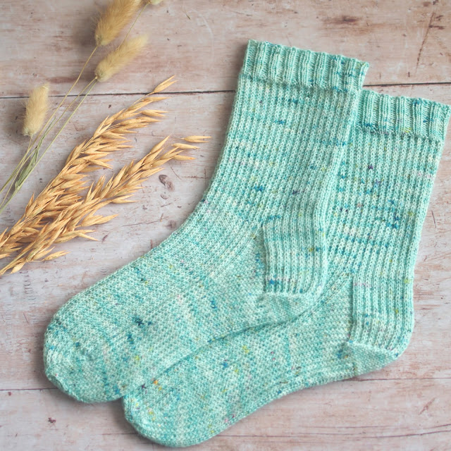 seafoam handnit socks with allover slipped stitch pattern laid flat with dried grass