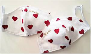 two white facemasks with red hearts on them.