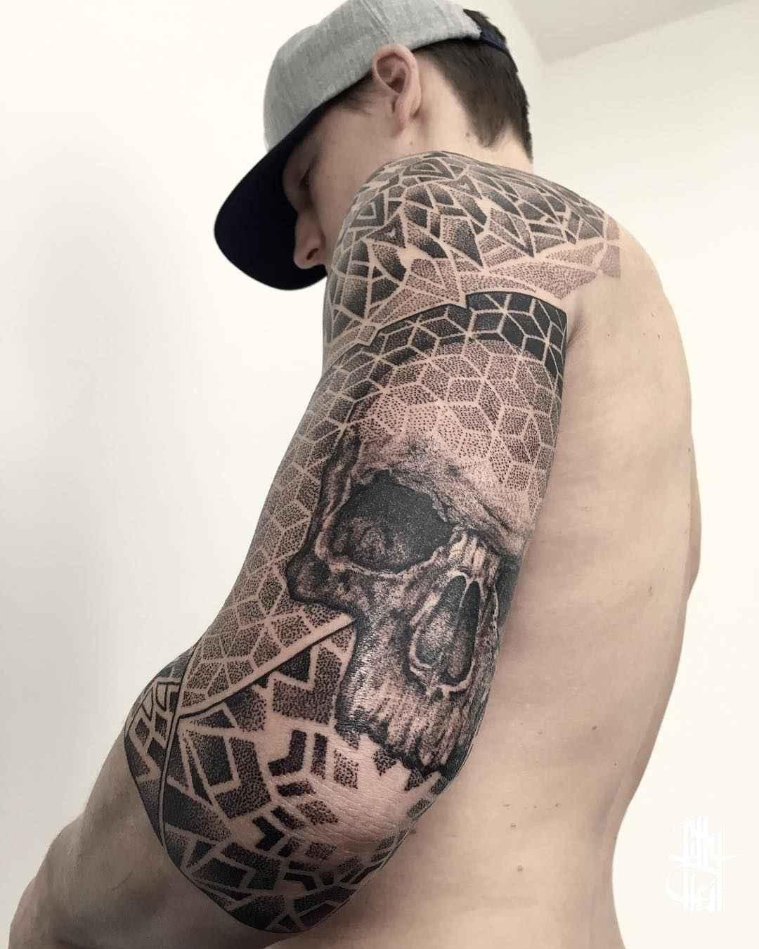 Un tatuaje geometrico en blanco y negro de calavera en el brazo