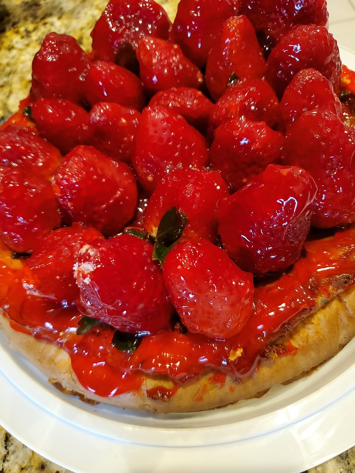 this is a baked cheesecake that is a ny style wit whole fresh strawberries glazed on top