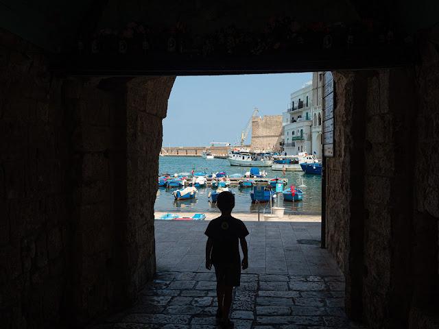 Niño pasando bajo un arco hacia el puerto de Monopoli con barcos de pesca al fondo