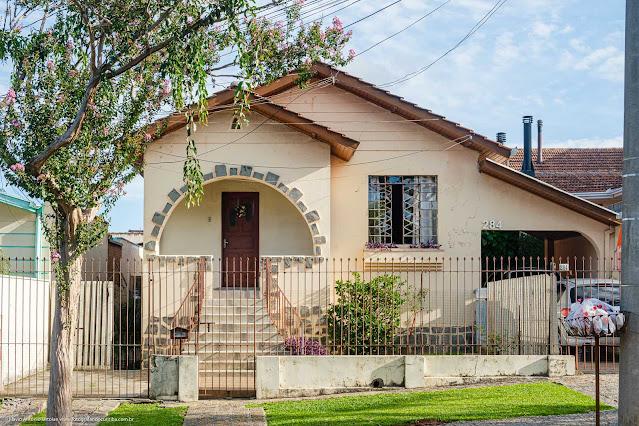 Casa com com varanda em arco decorado com basalto