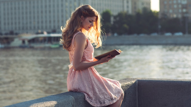 امرأة تقرأ كتاب عن قانون الجذب