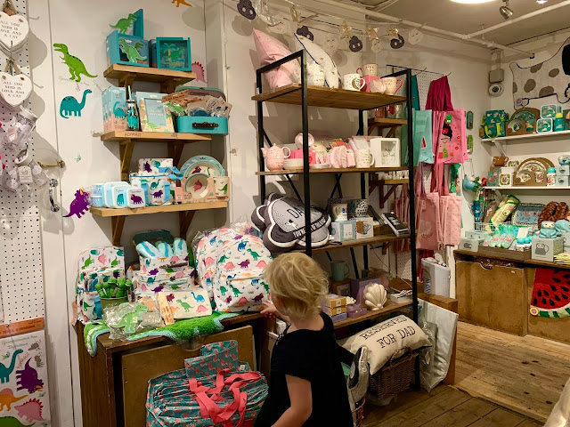 Child looking at dinosaur print bags in a covent garden shop