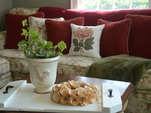 Cottage style floral couch with floral pillow, red pillows, floral wreath and ivy planter on tray.