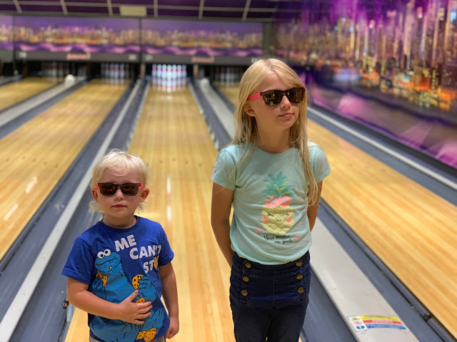 2 girls posing in sunglasses in front of bowling alleys