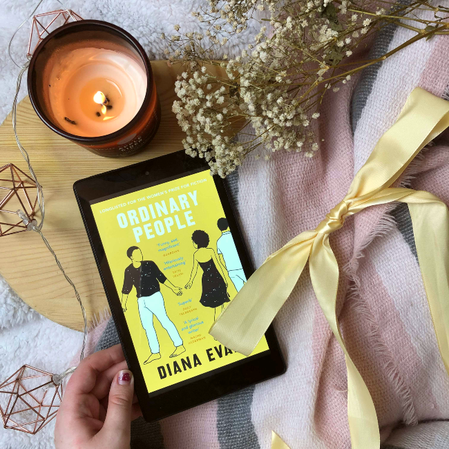 'Ordinary People' yellow book cover on a kindle next to a yellow ribbon and candle