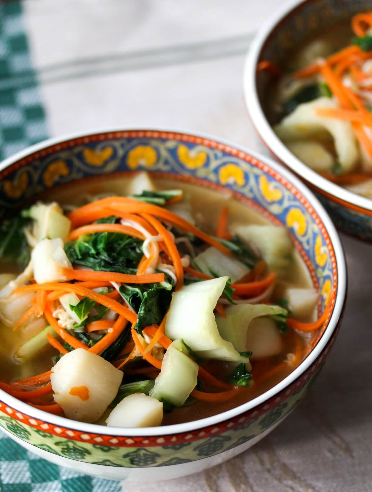 Bay scallop noodle soup with carrots in bowls.