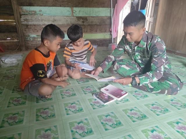 Anggota satgas TMMD mengajari anak anak untuk membaca dan menulis