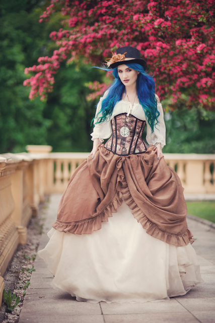 Woman wearing dreamy storybook steampunk clothing: corset, hat, blouse, skirt
