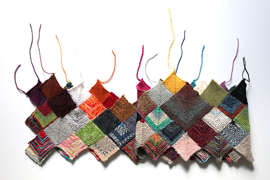 Colorful hand knit blanket made from sock weight wool scraps in mitered square blocks with unwoven ends sticking up on a white background.