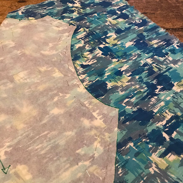 A sewing pattern on top of some fabric in various shades of blue