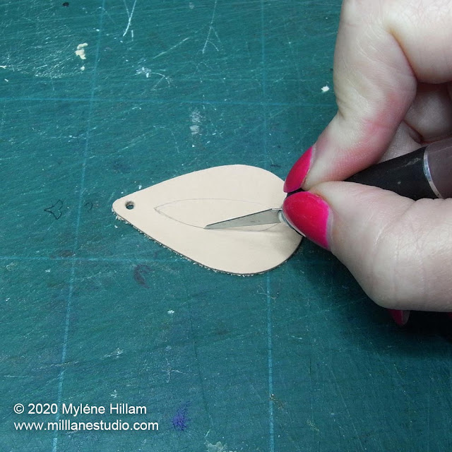 Cutting out the peep hole in the leather shape using a scalpel.