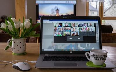 Skrivbord med dator där distansmöte pågår, blomvas och kaffekopp intill.