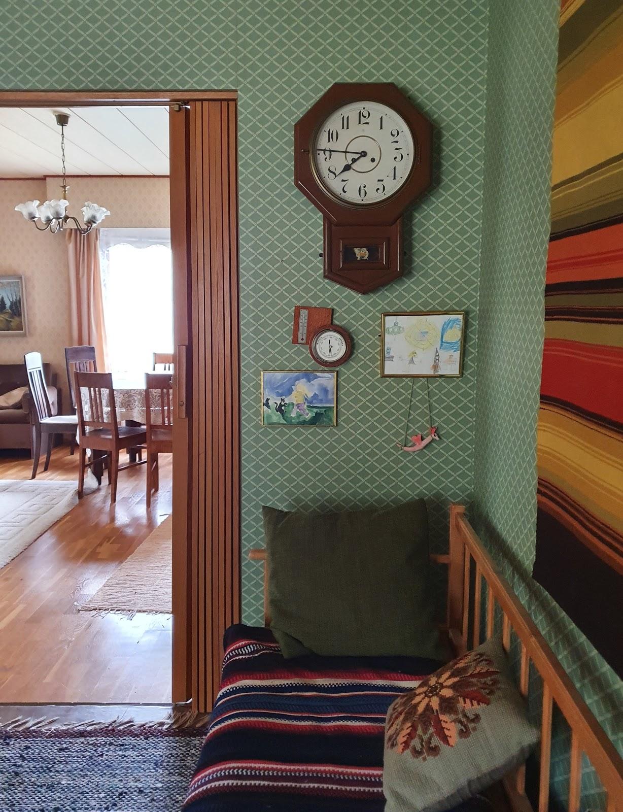 seinäkello ja piirroksia seinällä, taustalla olohuone