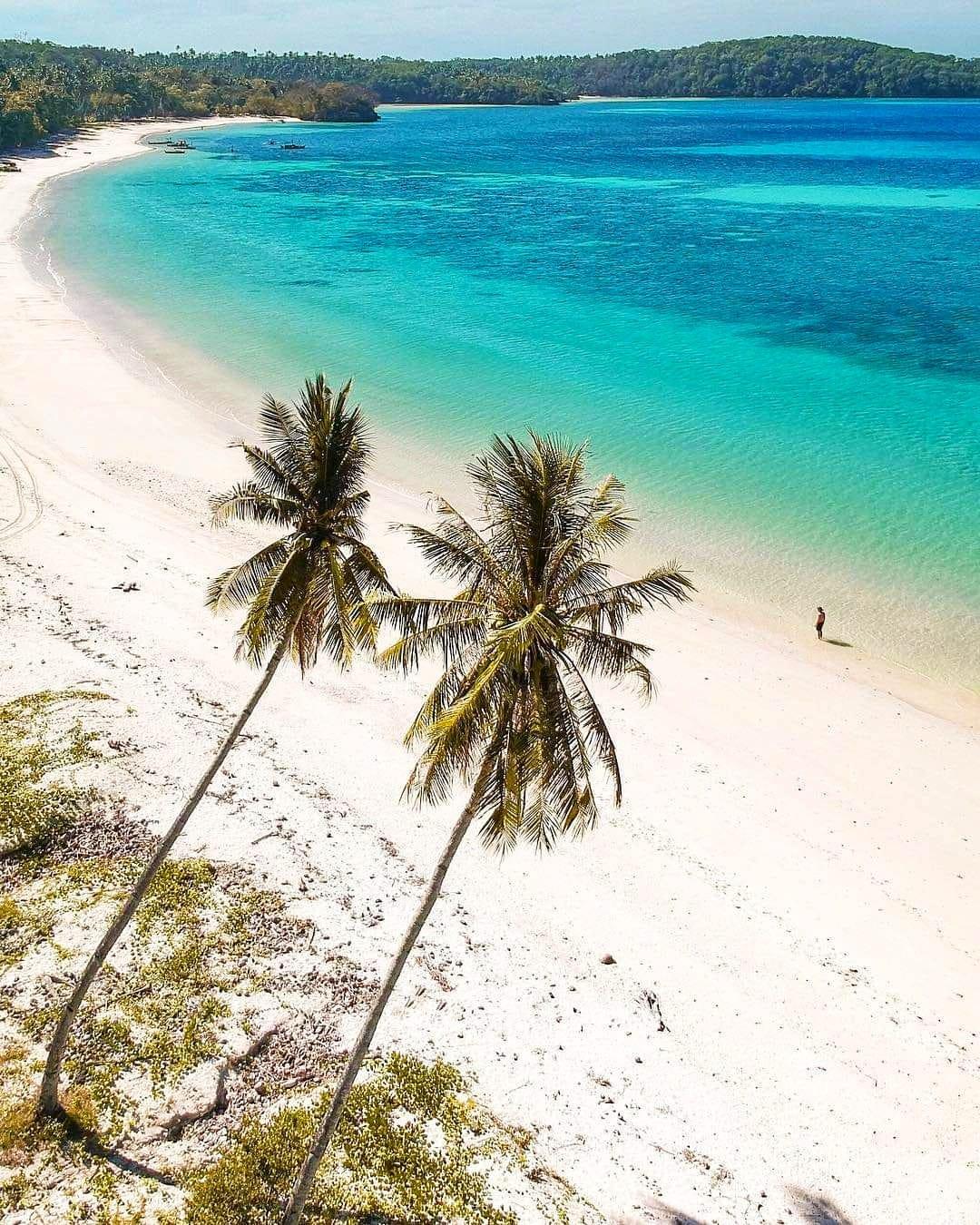 Gumasa Beach white san beach blue waters walking tourist palm trees