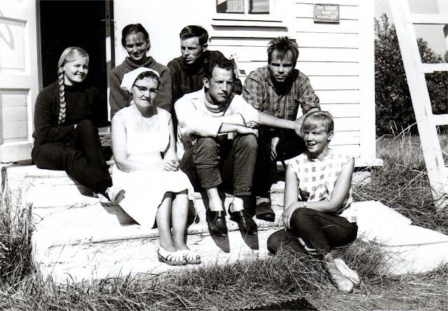 7 ihmistä istuu tutkimusaseman portailla kirkkaassa auringon paisteessa.