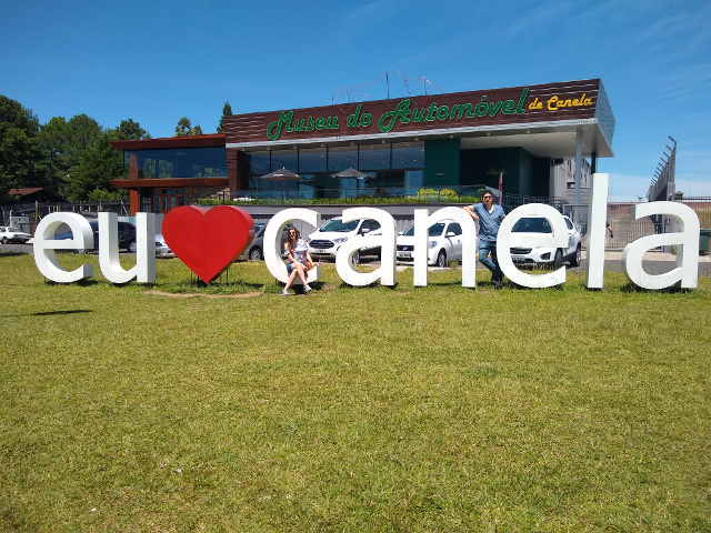 The sign that says Eu amo Canela in white with a heart in red with the automobile museum behind.