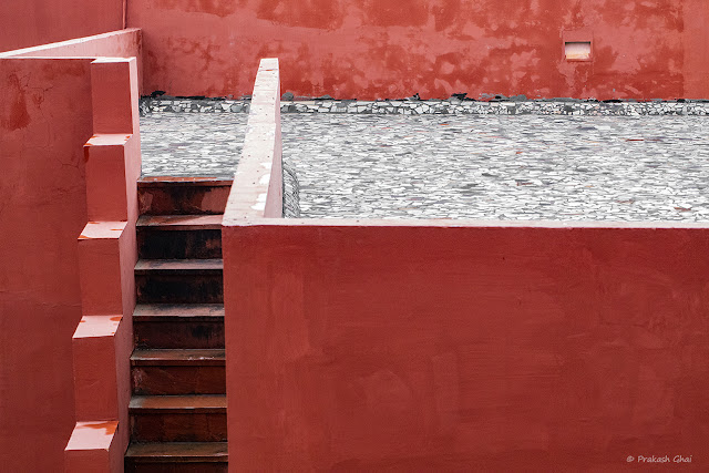 A Minimalist Photograph of a Steep Staircase and Red Walls at Jawahar Kala Kendra Jaipur.