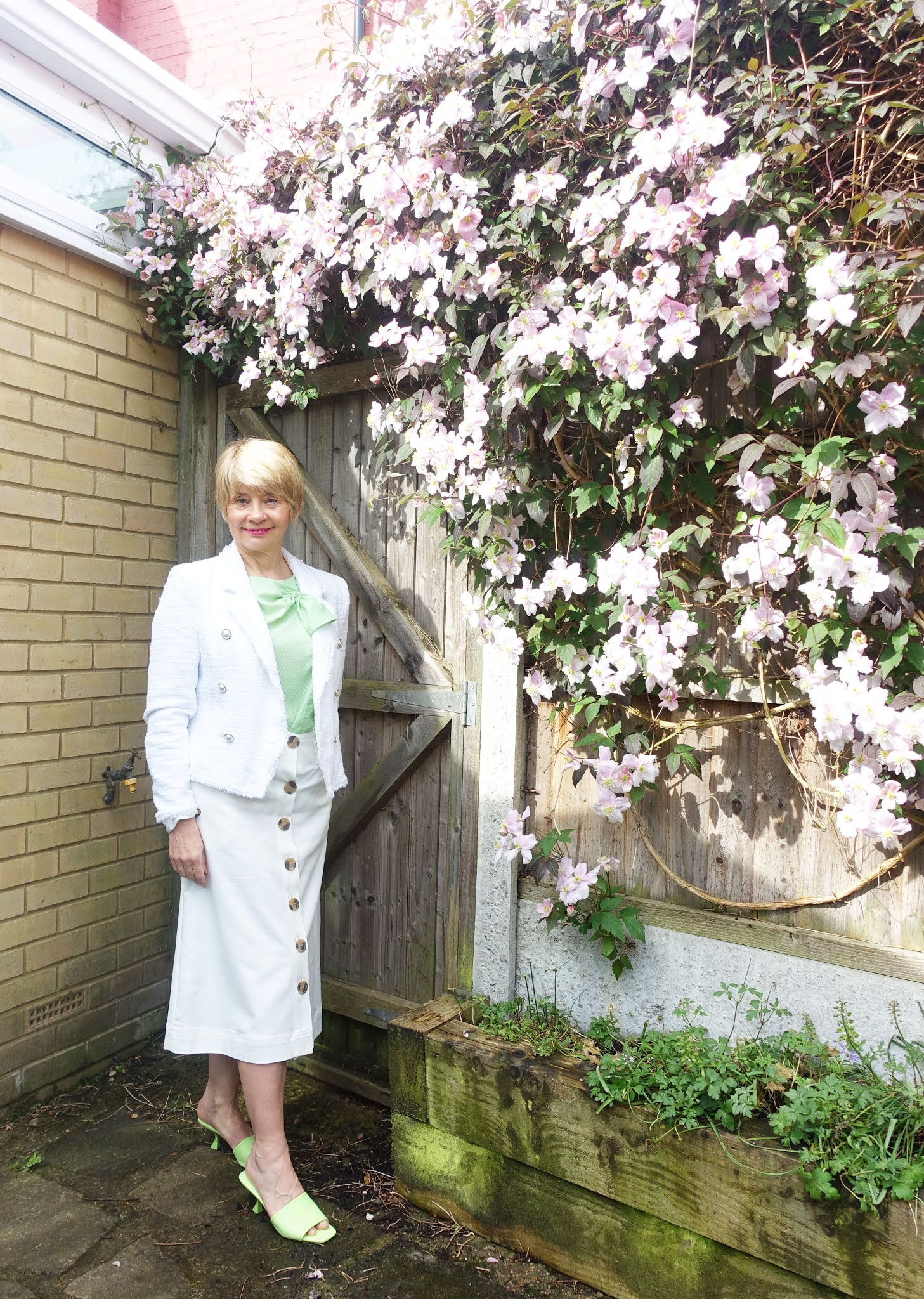 An all white outfit with green bow top and mules for over 50s blogger Gail Hanlon as she poses in the garden next to a pink clematis montana
