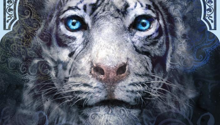 Imagem: um tigre branco de olhos azuis com ilustrações tipicamente indianas rodeando a figura formando mandalas e espirais em torno da figura.