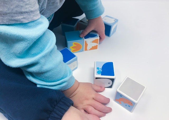 A close up of a toddler playing with the magicube set