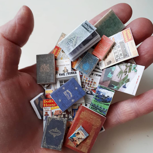 A hand covered with a selection of one twelfth scale miniature books and magazines