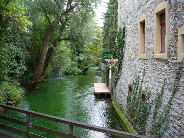 Die Pader fließt romantisch an der Stümpelschen Mühle vorbei. Links wachsen Bäume über den Fluss, rechts findet sich ein Steg und altes Mauerwerk eines Gebäudes.