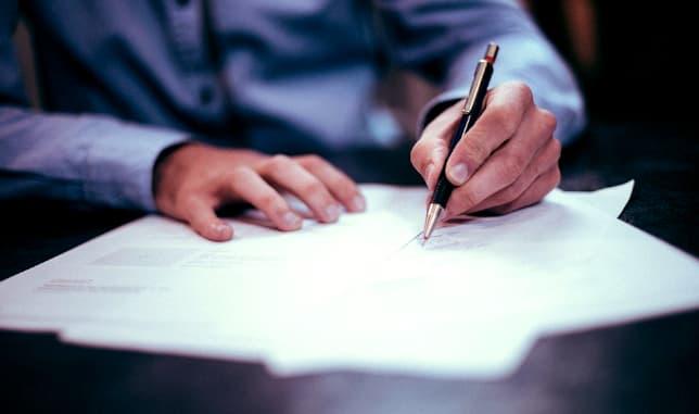 A imagem mostra as mãos de uma pessoa de camisa longa azul claro segurando uma caneta fazendo anotações em um caderno.