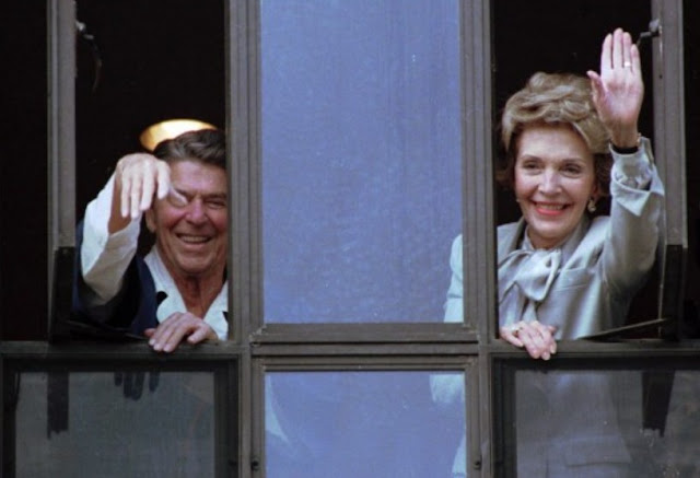 President Ronald Reagan and his wife, Nancy, wave from windows of his hospital room at the Navy Medical Center in Bethesda, Md., on July 18, 1985.