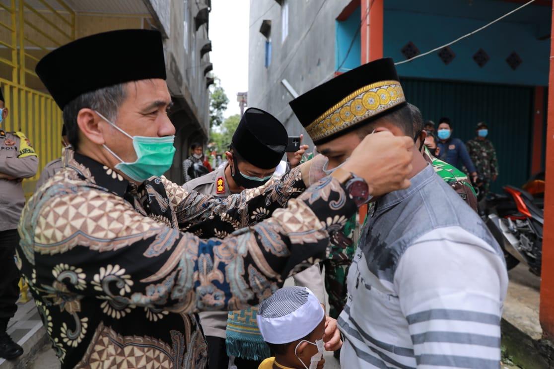 Bersama Dandim dan Kapolres,   Ketua DPRD Inhil, Riau Bagikan Masker Kepada Jamaah Shalat Jum'at