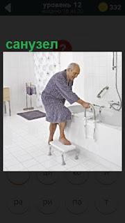 в санузле мужчина залезает в ванну держась руками за поручни