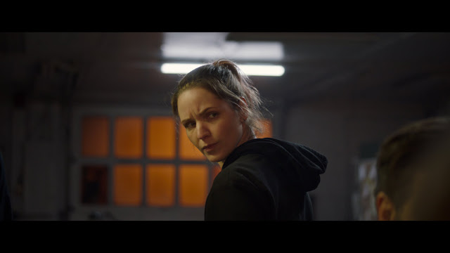 White woman in black hoodie looks over her shoulder