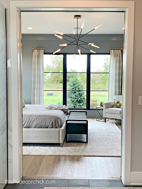 Modern gray master bedroom with large chandelier