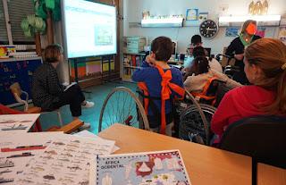 Alunos, pais e professora observam as imagens no quadro interativo