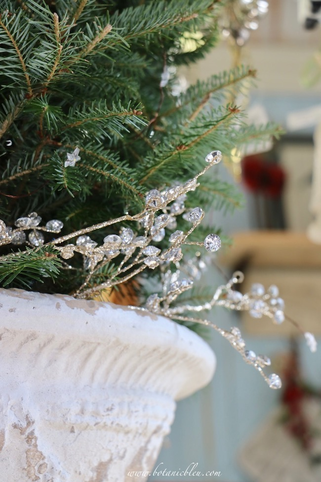 French Country Christmas Event 2019 has jewel glittered stems around the base of a fresh cut tree in a white pedestal urn