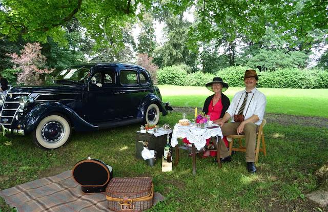 Oldtimer mit Frau und Mann an Picknick Tisch mit Kuchen unter Bäumen auf Schloss Merode