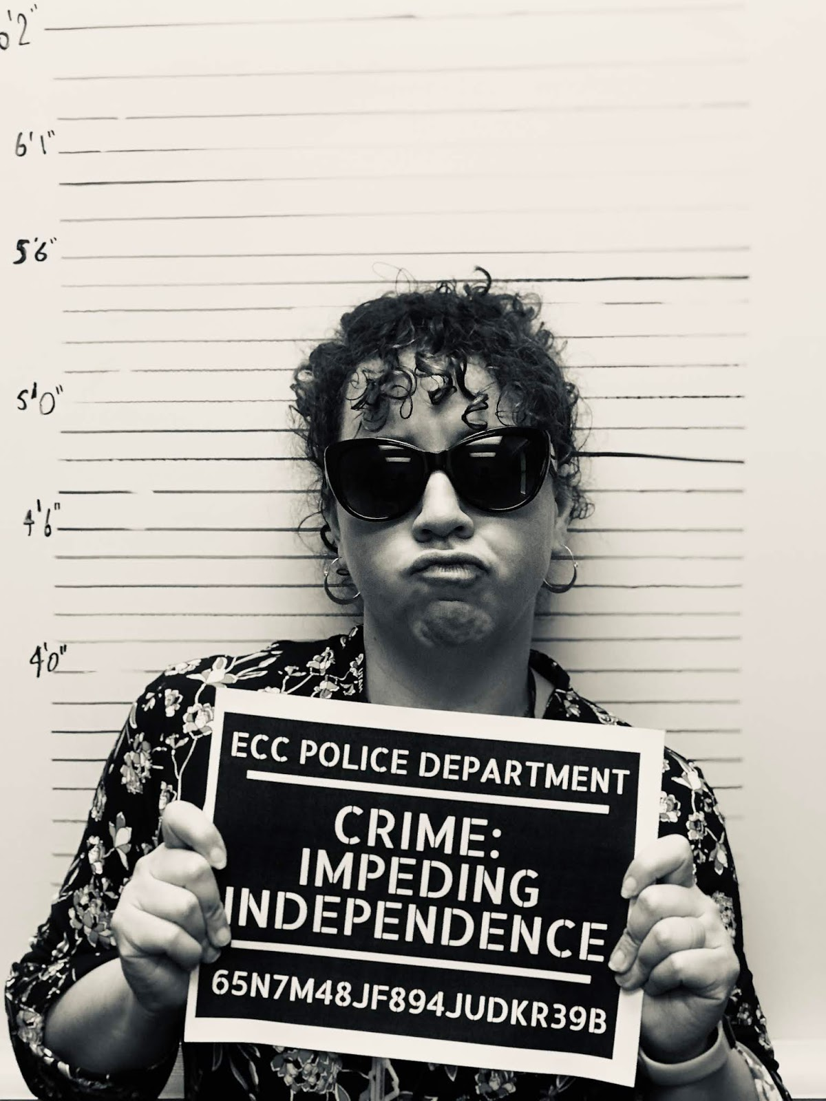 a mugshot of a female teacher wearing sunglasses with a tough expression