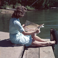 Lady seated by lake, reading